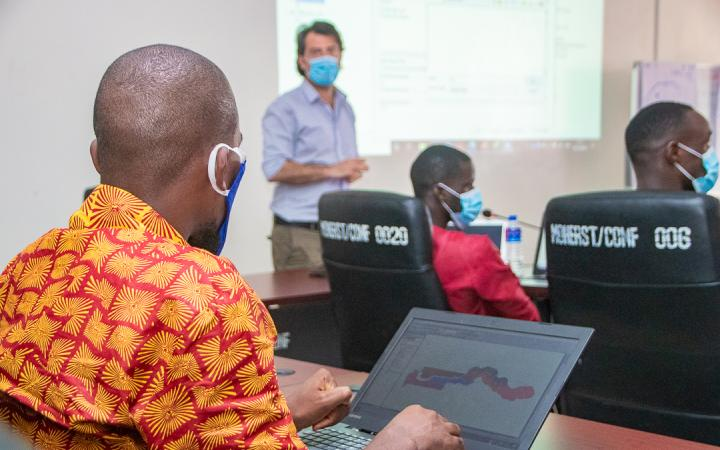 Back of a trainee wearing a face mask and view over his computer screen. In the background, trainer giving a presentation with a projector.