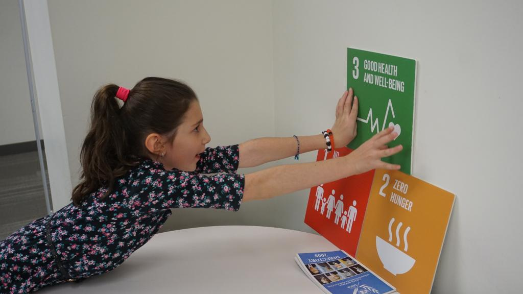 A participant posts signs describing the first three SDGs