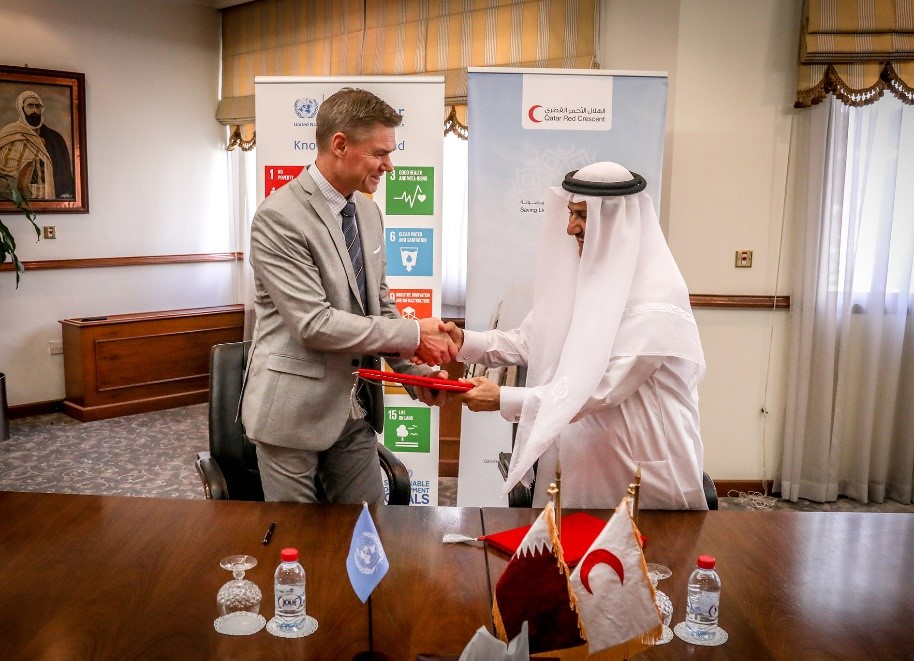 QRCS Secretary-General Ali bin Hassan and UNOSAT Manager Einar Bjorgo shake hands during the signing ceremony in Doha, Qatar